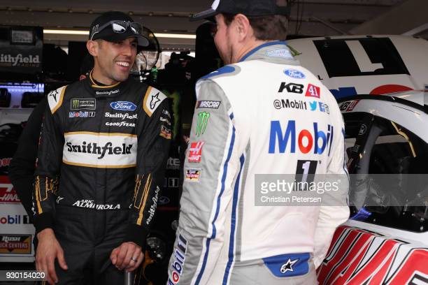 Aric Almirola driver of the Smithfield Ford talks to Kurt Busch driver of the Mobil 1/Haas Automation Ford in the garage area during practice for the...