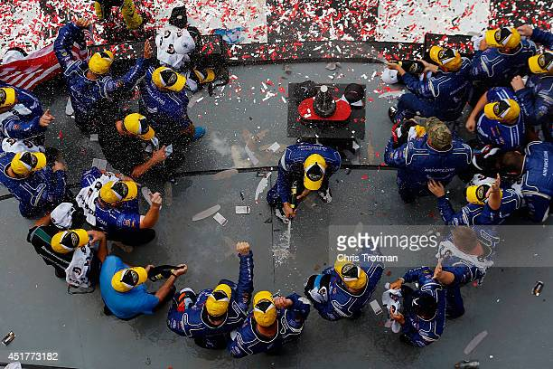 Aric Almirola driver of the United States Air Force Ford celebrates with champagne in Victory Lane after winning the NASCAR Sprint Cup Series Coke...