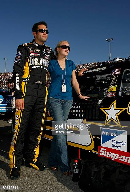Aric Almirola driver of the US ARMY Chevrolet and guest Janice Goss stand on the grid during the national anthem for the NASCAR Sprint Cup Series...