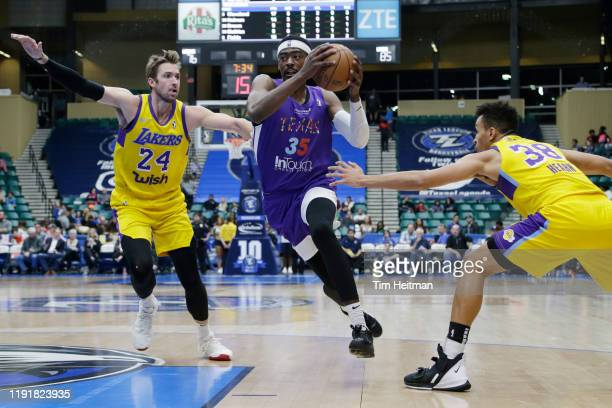 Aric Holman of the Texas Legends drives on Travis Wear of the South Bay Lakers and Reggie Hearn of the South Bay Lakers in the third quarter on...