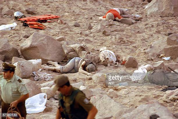 Rescuers work amid the scattered bodies of the passengers of a tourist bus that fell over a precipice 22 March 2006 in the Lauca National Park near...
