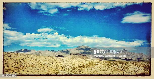 arid landscape against cloudy sky - boulder city stock photos and pictures