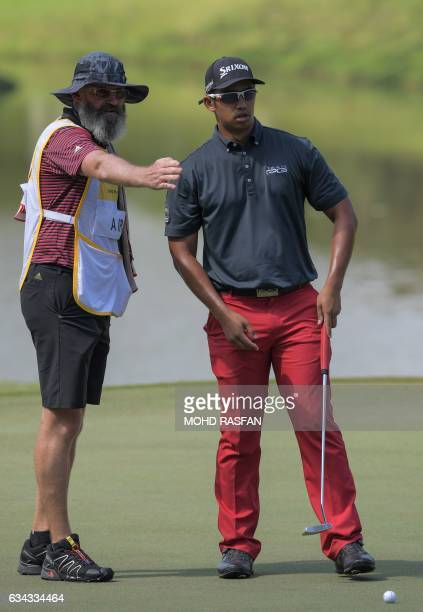 Arie Irawan of Malaysia listens to his caddie before putting during the first round of the 2017 Maybank Malaysia Championship golf tournament at...