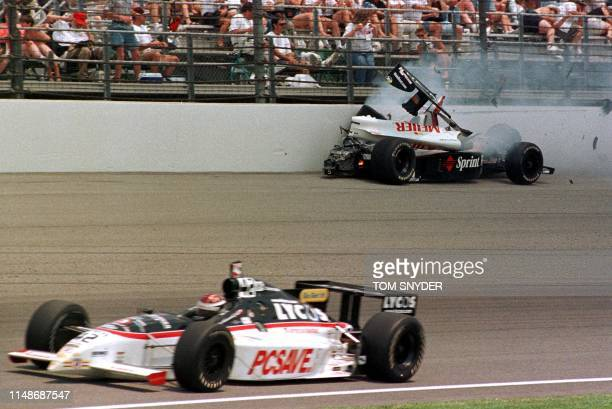 Arie Luyendyk of Holland crashes into the wall as John Hollansworth Jr of the US drives by 30 May 1999 during the 83rd Indianapolis 500 at...