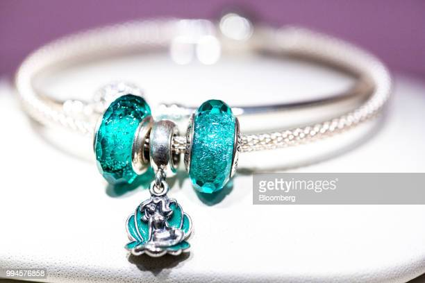 Ariel a character from Walt Disney Co's Little Mermaid movie sea shell pendant charm center sit on a bracelet on display in a Pandora A/S store in...