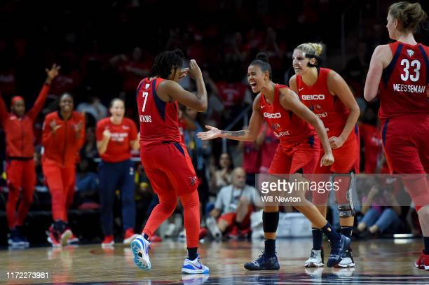 Ariel Atkins of the Washington Mystics celebrates with Natasha Cloud and Elena Delle Donne after a play against the Connecticut Sun during the second...