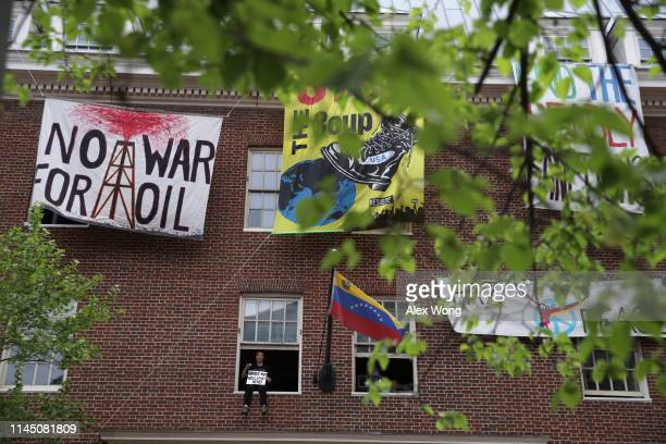 Ariel Gold of CodePink sits on a window of the Embassy of Venezuela during a news conference April 25 2019 in Washington DC About a dozen of...