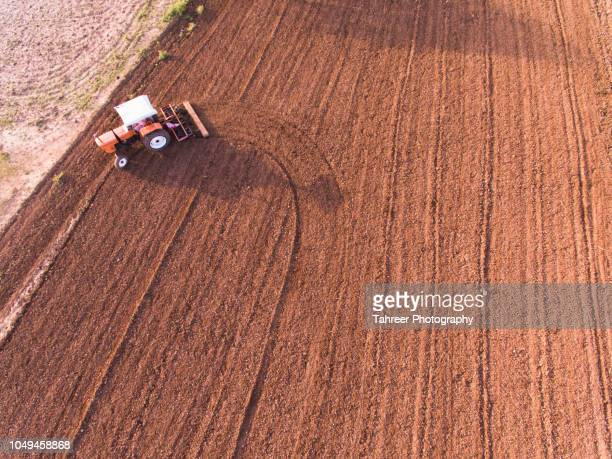ariel image of a tractor plowing the fields - crop circle photos et images de collection