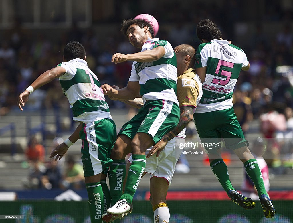 Ariel Nahuelpan (L) of Pumas fights for the ball with Cesar Ibanez of Santos during a match between Pumas and Santos as part of the Apertura 2013 Liga MX at Olympic Stadium on October 06, 2013 in Mexico City, Mexico.