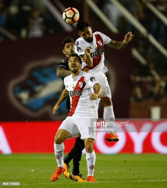 Ariel Rojas and Ignacio Scocco of River Plate fight for the ball with Roman Martinez of Lanus during a second leg match between Lanus and River Plate...