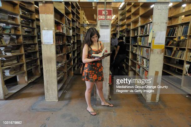USA Ariel Sanchez takes a moment to read a book as her friends search for treasures to fill their crate during Acres of Books' last hurrah in Long...
