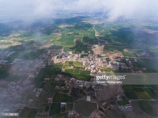 ariel view of cultivated agriculture fields and village - harlequins stock pictures, royalty-free photos & images