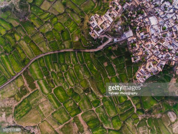 ariel view of road entering the village from arid land - sustainable development goals stock pictures, royalty-free photos & images