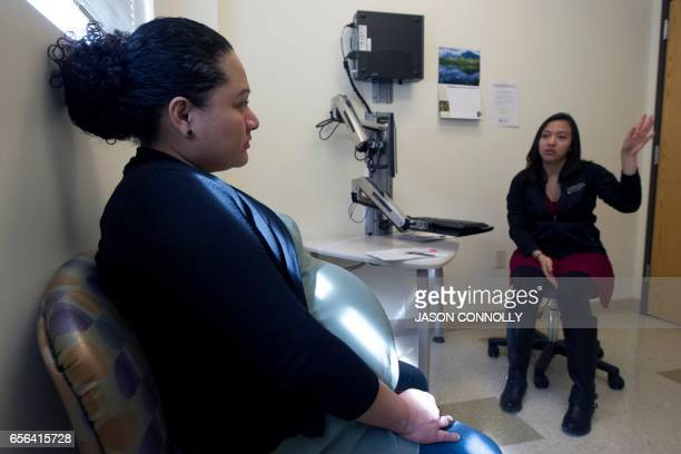 Ariel Zetina listens as Andrea Cortez a volunteer EMT at Inner City Health Center in Denver Colorado discuss Zetina's pregnancy on March 15 2017...