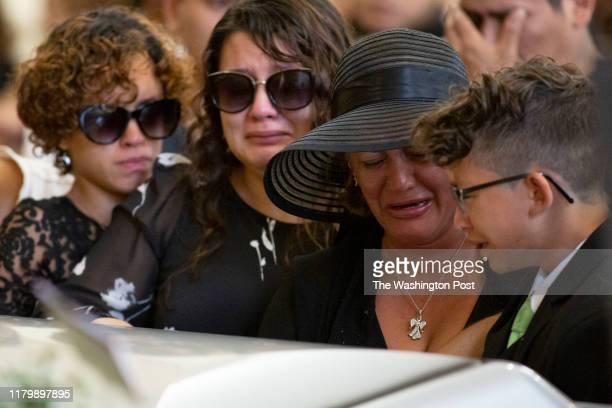 Ariela LoboPerez Jennifer Turcios Dixiana Dixie Perez and Erick Bubu LoboPerez close the casket during the funeral for Aris Eduardo LoboPerez at...