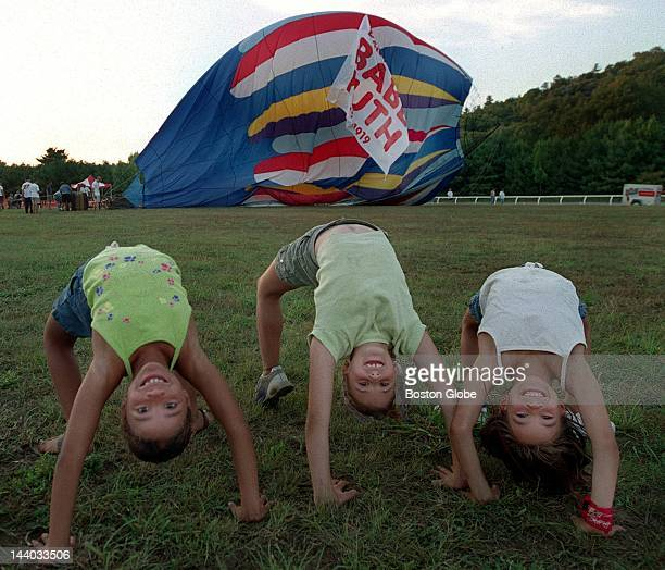 Arielle Correia Leah Zysman and Julie Fanara all do back flips during the lifting of the hot air balloon that was brought in to lift the Curse of the...