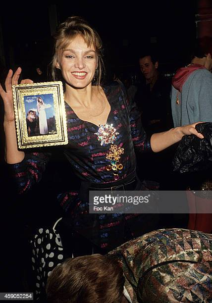 Arielle Dombasle poses with her portrait by Pierre et Gilles at a party at Les Bains Douches in the 1990s in Paris France