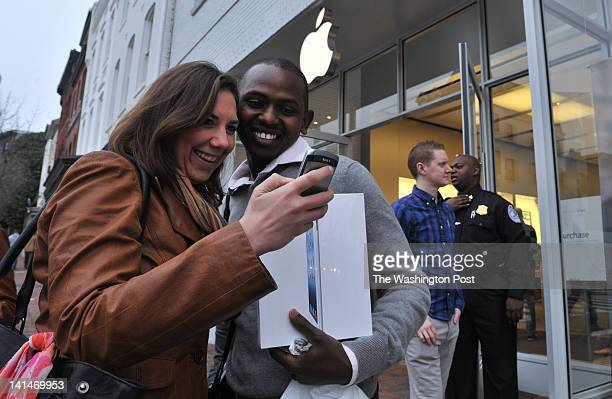 Arielle Molino L of DC and Abdallah Mohamed on a business trip from Kenya view a picture of Mohamed holding his new iPad 3 in front of Apple's...