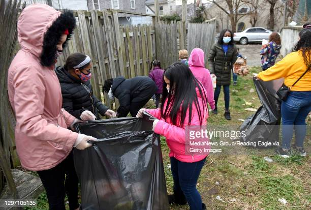 Ariely Rodriguez and Frances Perez hold the trash bag as other club members put trash in. At the Olivet Boys and Girls Club Mulberry Street location...