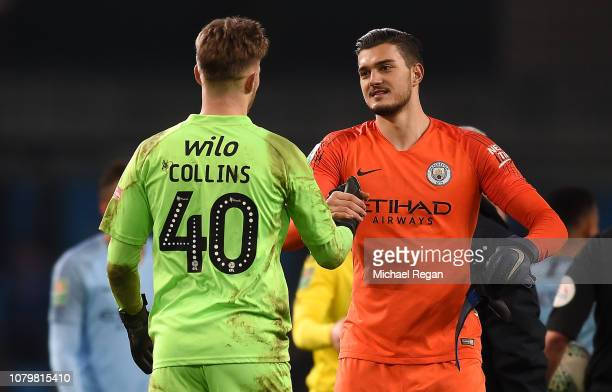Arijanet Muric of Manchester City consoles Bradley Collins of Burton Albion after the Carabao Cup Semi Final First Leg match between Manchester City...