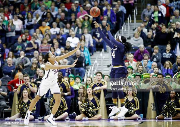 Arike Ogunbowale of the Notre Dame Fighting Irish hits the game winning shot with 1 second left in overtime under pressure from Napheesa Collier of...