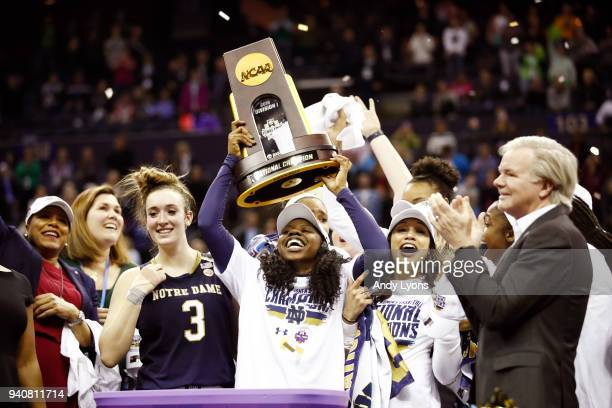 Arike Ogunbowale of the Notre Dame Fighting Irish hoist the NCAA championship trophy after scoring the game winning basket to defeat the Mississippi...