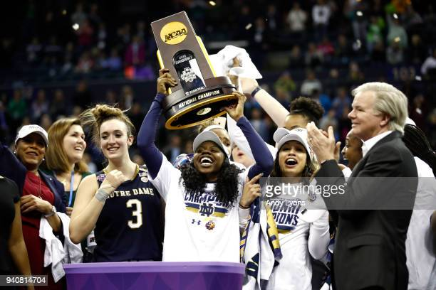 Arike Ogunbowale of the Notre Dame Fighting Irish hoists the NCAA championship trophy after scoring the game winning basket to defeat the Mississippi...