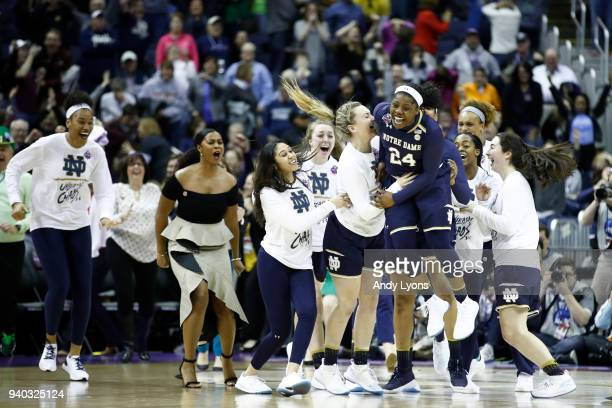 Arike Ogunbowale of the Notre Dame Fighting Irish is congratulated by her teammates after hitting the game winning basket to defeat the Connecticut...