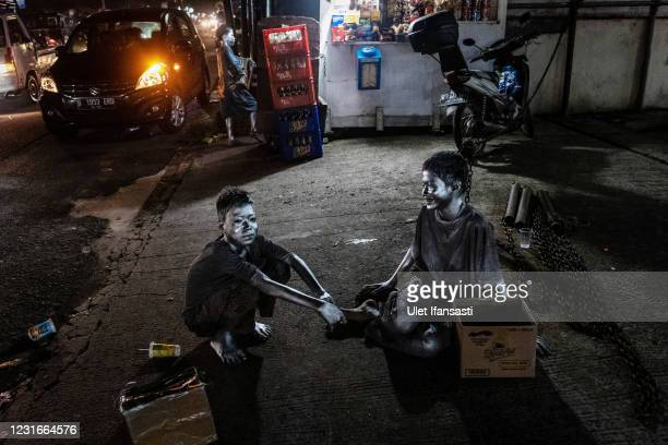 """Aril and Angga , wearing silver paint take a rest as they beg on the street on March 11, 2021 in Depok, Indonesia. 'Silver Men', called """"Manusia..."""