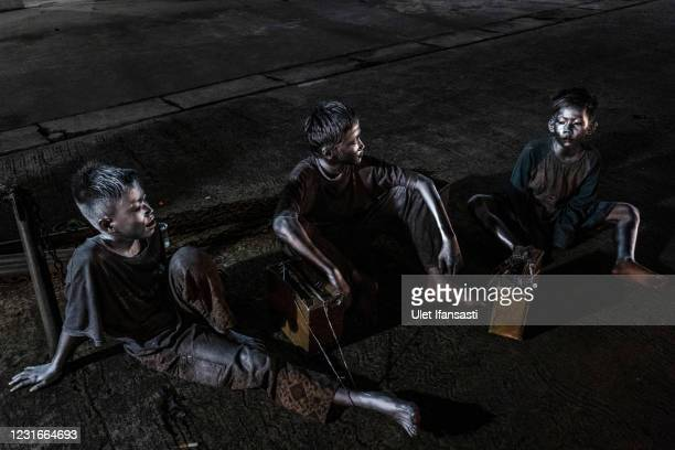 Aril , Angga and Rendi , wearing silver paint take arest as they beg on the street on March 11, 2021 in Depok, Indonesia. 'Silver Men', called...