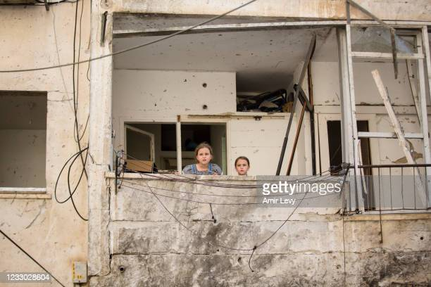 Arina and Zoya Klochkov stand in their damaged house after a rocket fired from the Gaza Strip hit earlier this week on May 21, 2021 in Sderot,...