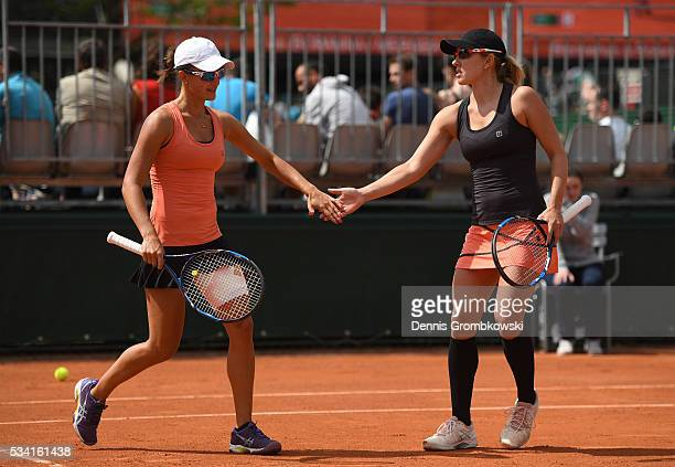 Arina Rodionova and Anastasia Rodionova of Australia high five during the Womens Double first round match against Timea Babos of Hungary and...