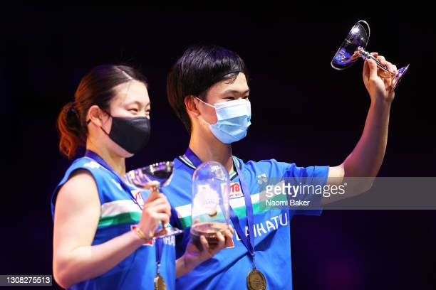 Arisa Higashino and Yuta Watanabe of Japan celebrate on the podium after their victory in the mixed doubles final against Yuki Kaneko and Misaki...