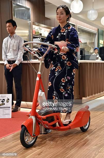 Arisa Katayama an employee of Japan's auto parts maker Katayama Kogyo demonstrates the company's electric motorassisted standing style tricycle...