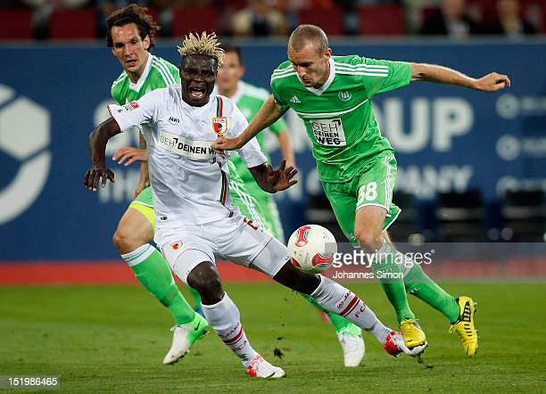 Aristide Bance of Augsburg fights for the ball with Thomas Kahlenberg and Emanuel Pogatetz and of Wolfsburg during the Bundesliga match between FC...
