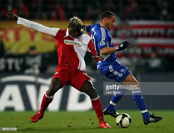 """Aristide Bance of Mainz challenges Jermaine Jones of Schalke during the DFB Cup quarter final match between FSV Mainz 05 and FC Schalke 04 at the """"Am..."""