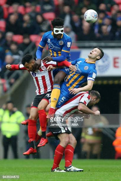 Aristote Nsiala and Mat Sadler of Shrewsbury Town challenge for the ball with Matt Green and Matt Rhead of Lincoln City during the Checkatrade Trophy...