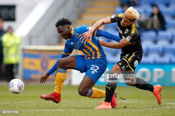 Aristote Nsiala of Shrewsbury Town competes with Lyle Taylor of AFC Wimbledon during the Sky Bet League One match between Shrewsbury Town and AFC...