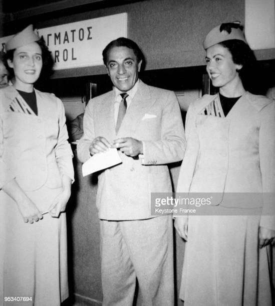 Aristote Onassis photographié entre deux charmantes hôtesses à l'aéroport d'Athènes Grèce le 7 décembre 1959