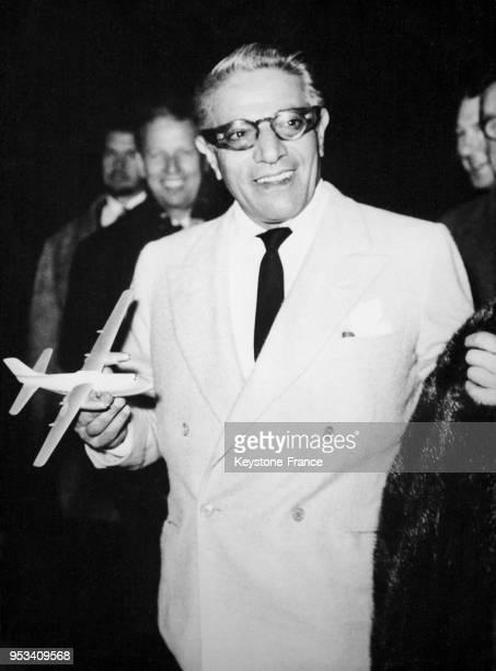 Aristote Onassis tout sourire tient dans ses mains un avion miniature à son arrivée à Londres RoyaumeUni le 5 décembre 1959