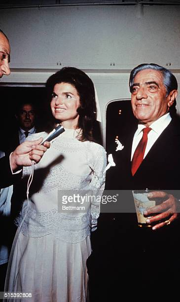 Aristotle Onassis married Jackie Kennedy on his private island. Onassis is shown with a drink in his hand and Jackie is smiling and talking into a...
