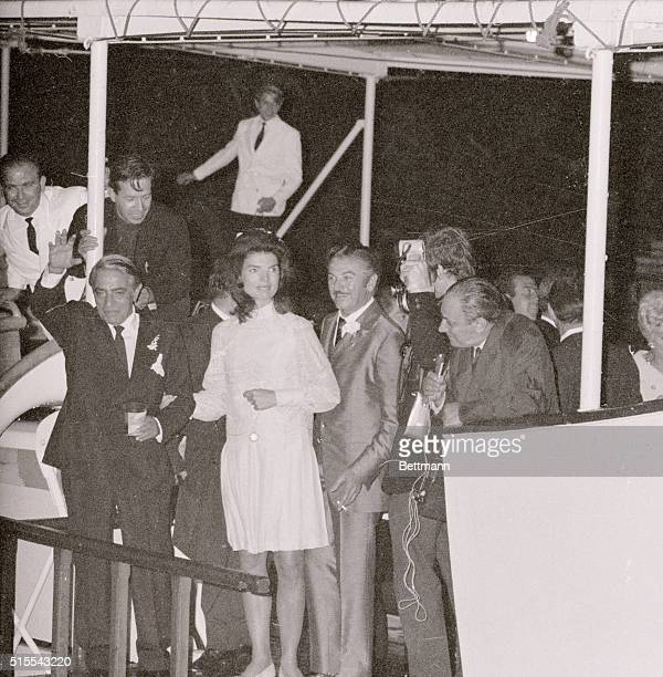 Aristotle Onassis with his bride Jacqueline Kennedy by his side waves from his yacht Christina after their wedding on the Isle of Skorpios | Location...