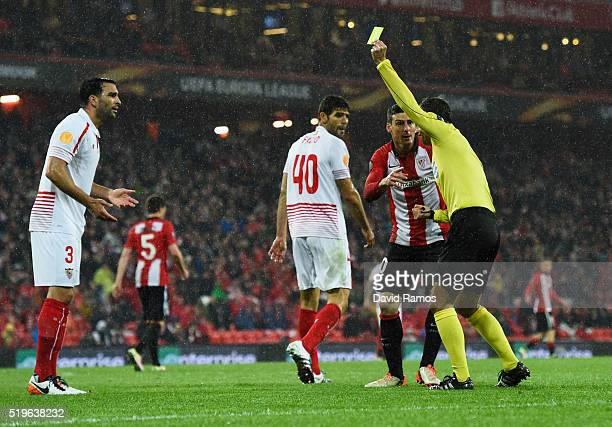 Aritz Aduriz of Athletic Club Bilbao appeals as referee Mark Clattenburg shows a yellow card to Adil Rami of Sevilla during the UEFA Europa League...