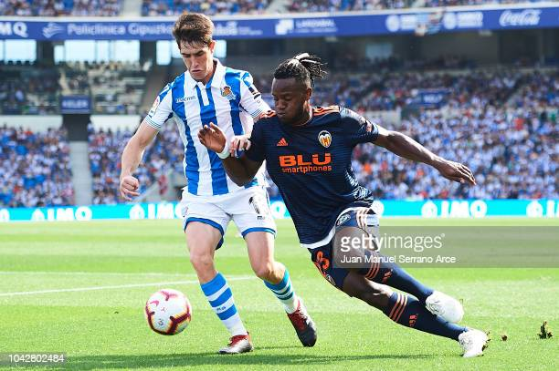 Aritz Elustondo of Real Sociedad competes for the ball with Michy Batchuayi of Valencia CF during the La Liga match between Real Sociedad and...