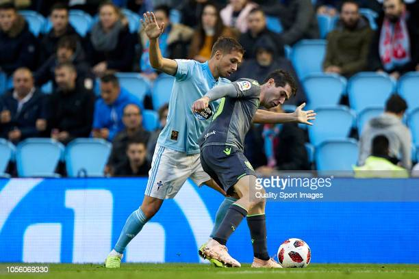 Aritz Elustondo of Real Sociedad is challenged by Andrew Hjulsager of Celta de Vigo during the Spanish Copa del Rey match between Real Club Celta v...