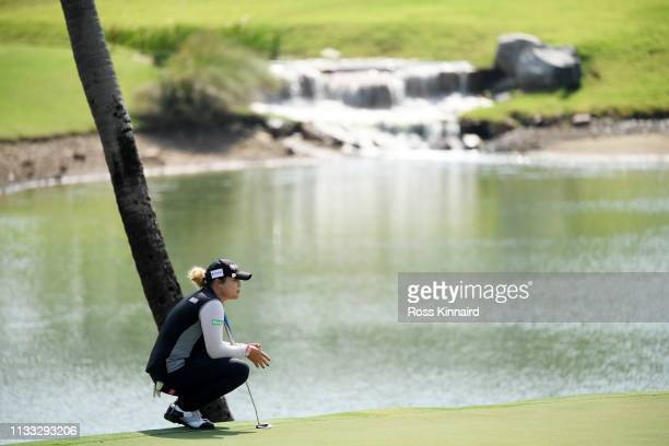 Ariya Jutanugarn of Thailand lines up a putt on the second green during the final round of the HSBC Women's World Championship at Sentosa Golf Club...