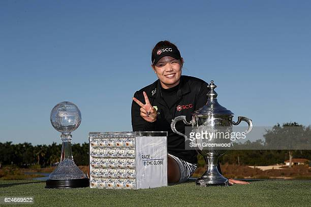 Ariya Jutanugarn of Thailand poses with the Rolex Player of the Year trophy the CME Race for the Globe trophy and a box of one million dollars in...