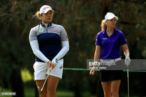 Ariya Jutanugarn of Thailand watches her shot on the third tee as Amy Anderson of the United States looks on during the first round of the...