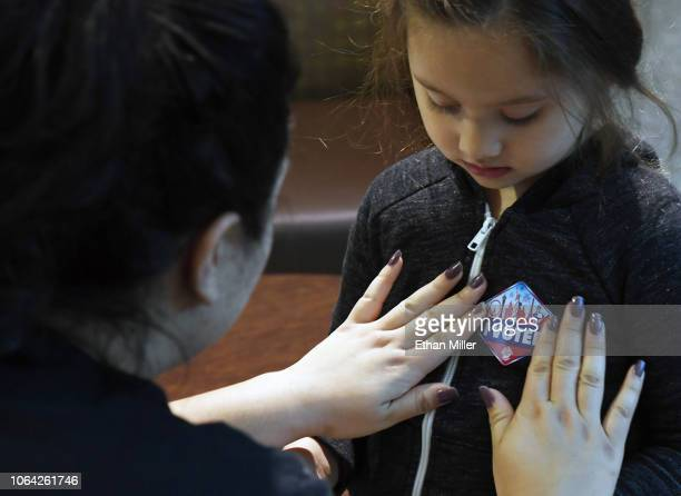 Ariyonna Munshack of Nevada puts her I Voted sticker on her cousin Emma Henderson after voting at the Galleria at Sunset mall on November 6 2018 in...