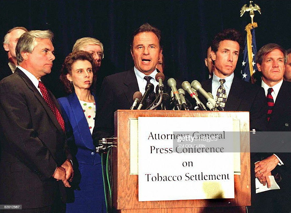 Arizona Attorney general Grant Woods (speaking), along with Mississippi Attorney General Mike Moore (2nd-R), Massachusetts Attorney General Scott Harshbarger (R) and others speak to reporters during a news conference 20 March in Washington, DC, to discuss a settlement with the tobacco company the Liggett Group, Inc. Liggett admitted for the first time that cigarette makers knew of the dangers of smoking, and settled expensive litigation in 22 states.
